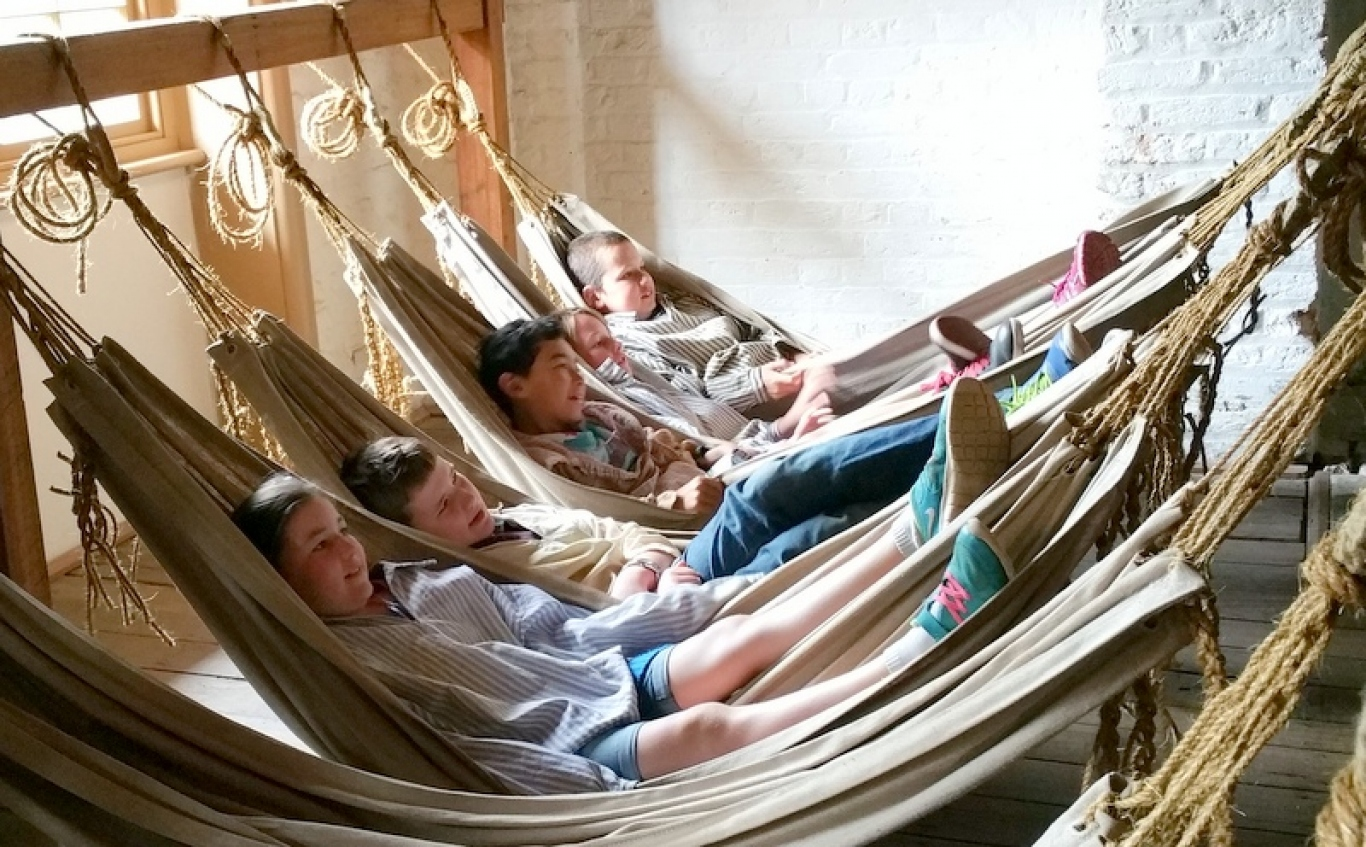 Childen lying in canvas hammocks strung up using rope tied to wooden beams.