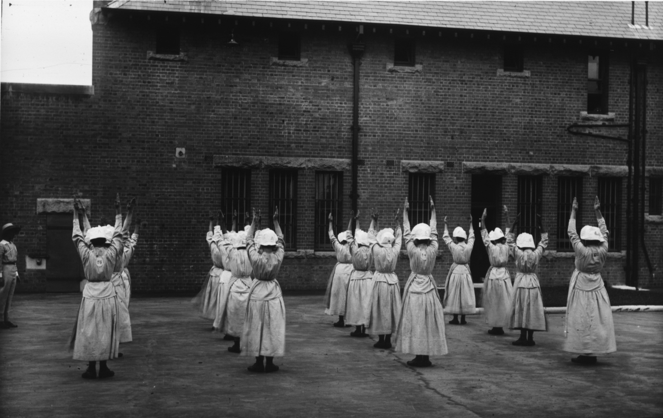Black and white photo of group of women in courtyard doing stretches, wearing white bonnets, with backs to camera.