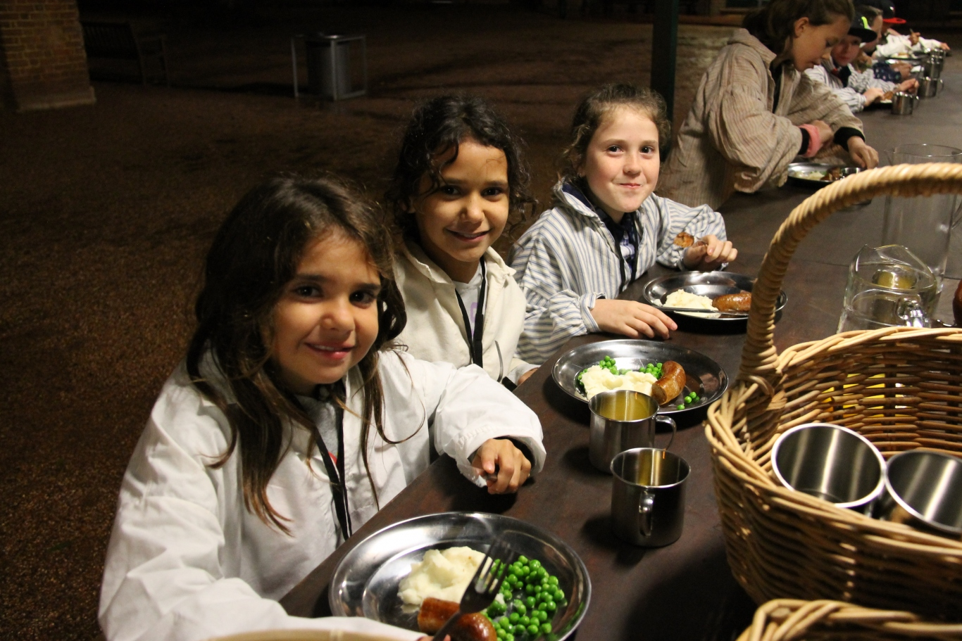 Children dressed in convict costume seated at long table with food and drink.