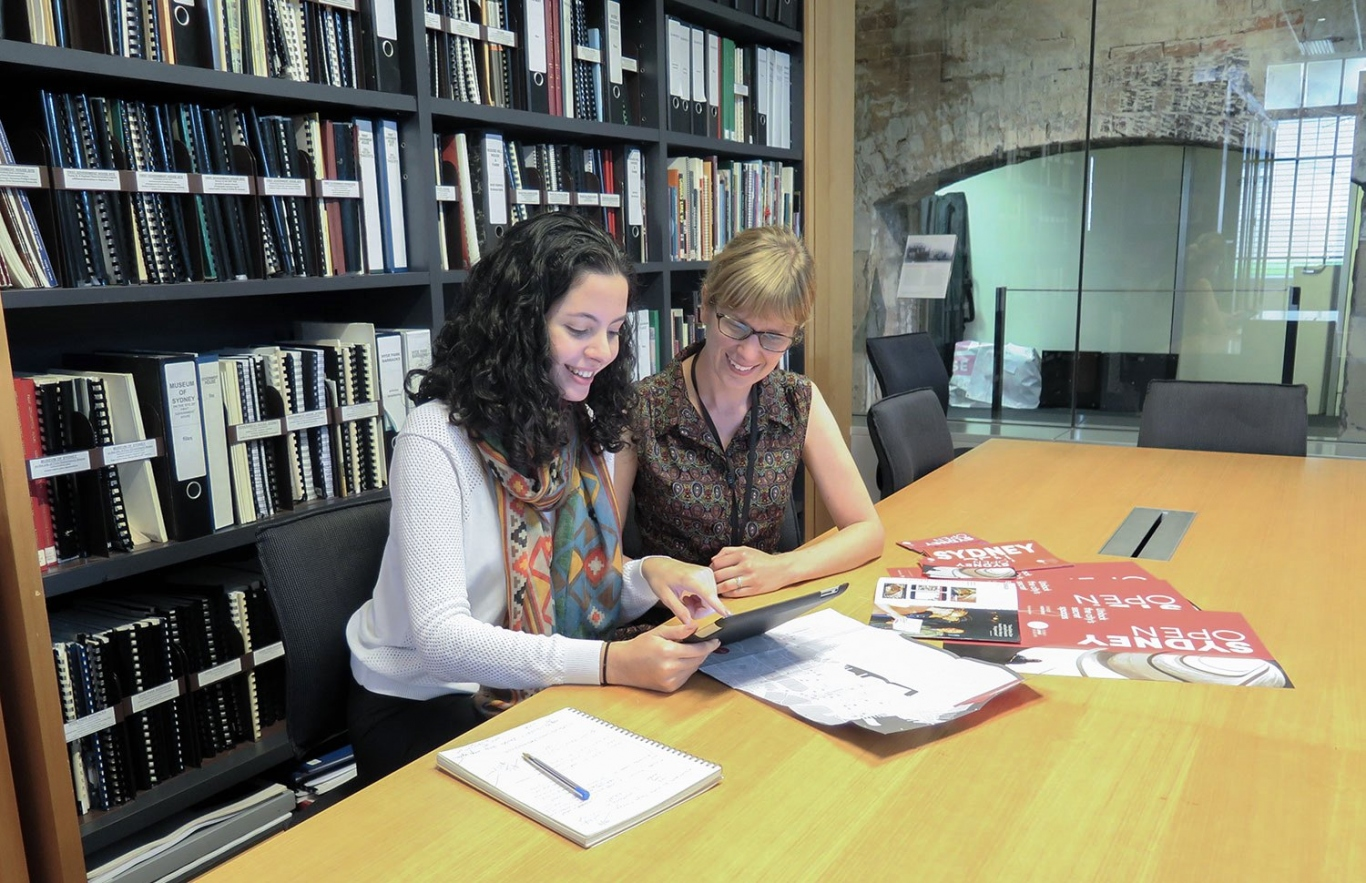 Two young women seated at long table with ipad and brochures, with wall of books behind.