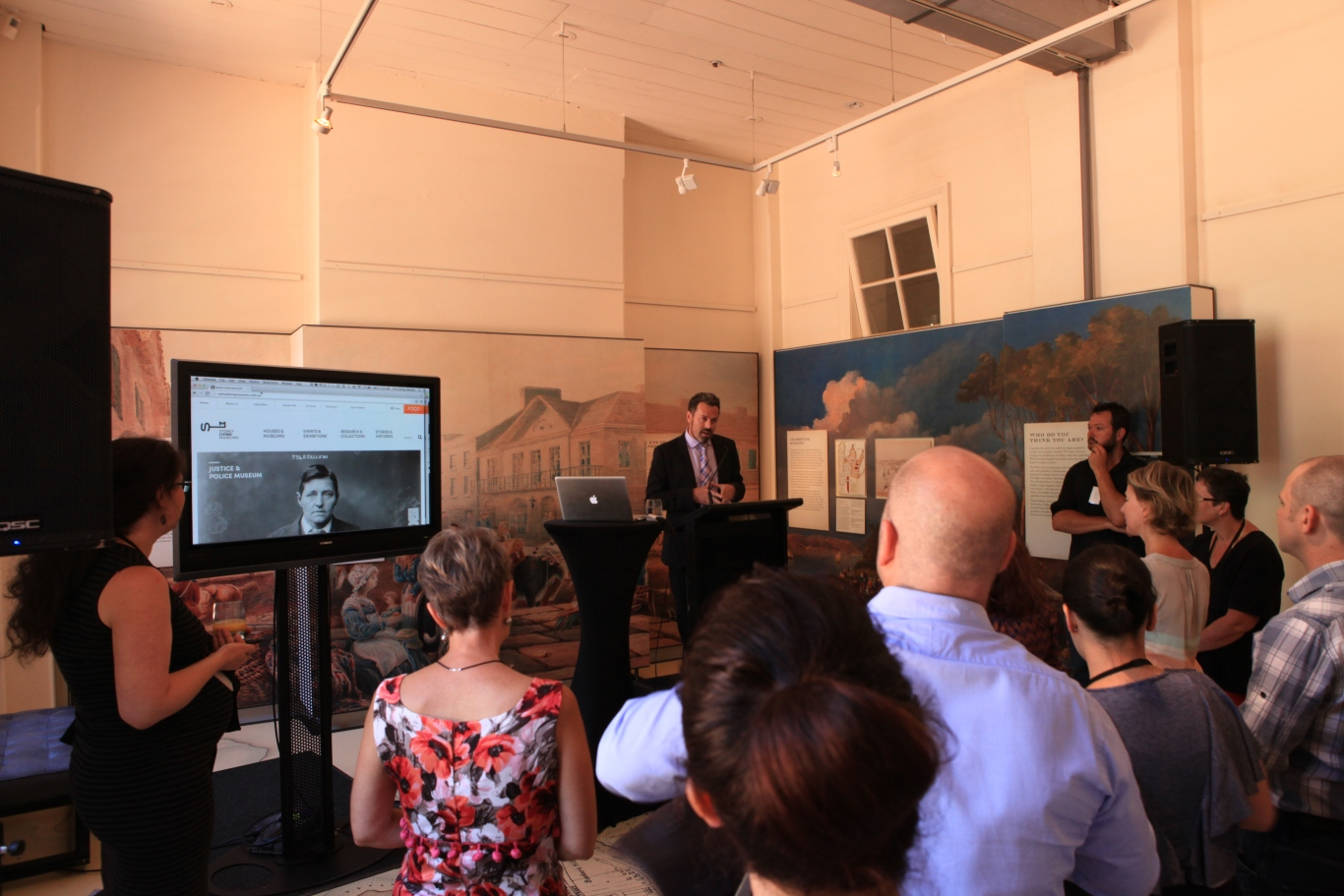 Photo showing SLM director Mark Goggin speaking to a crowd of people. He is standing on a podium with a large screen showing the website to his right.