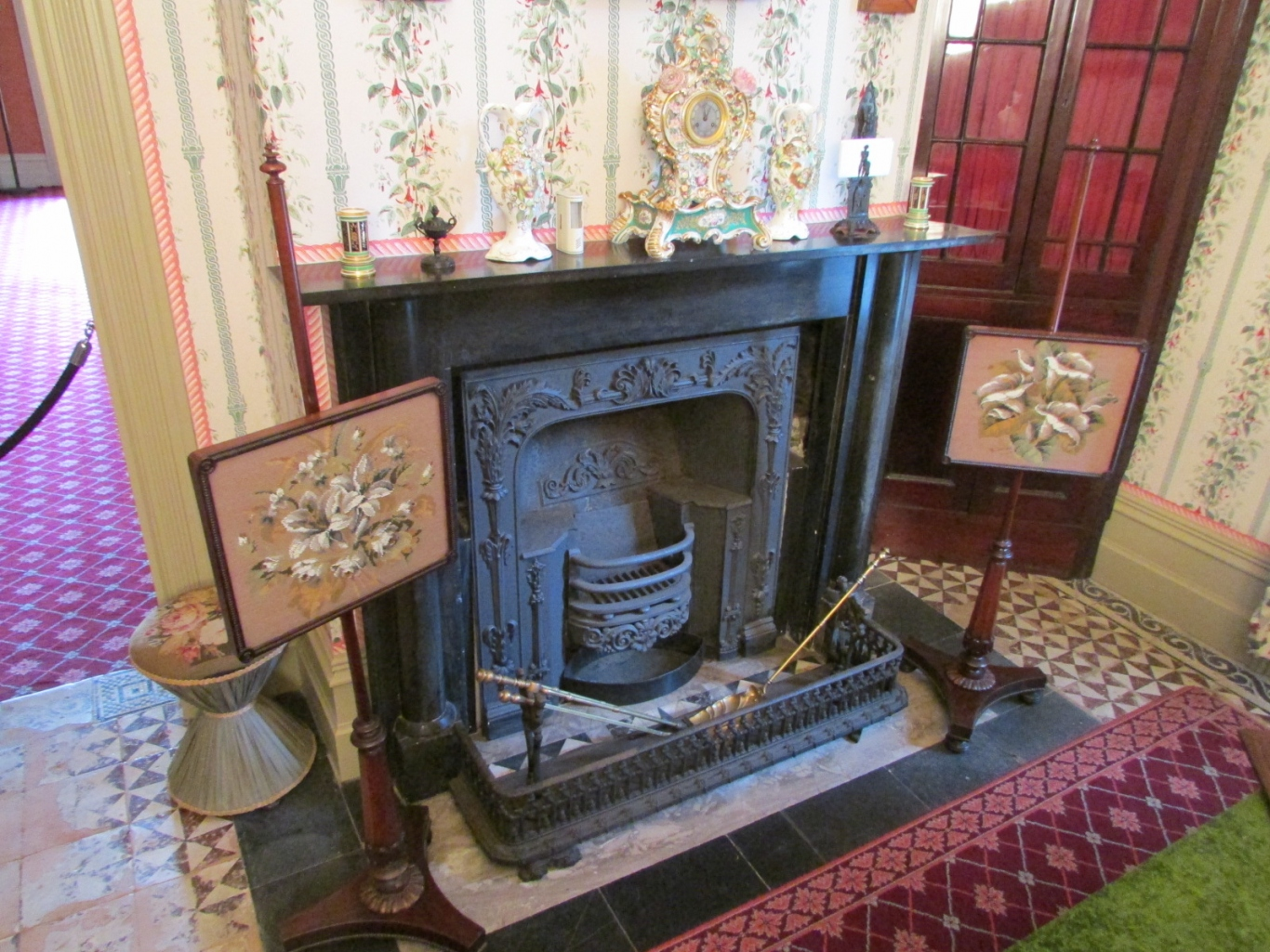 Fireplace flanked by two ornate screens and surrounded by a fender and grate, with mantelpiece above.