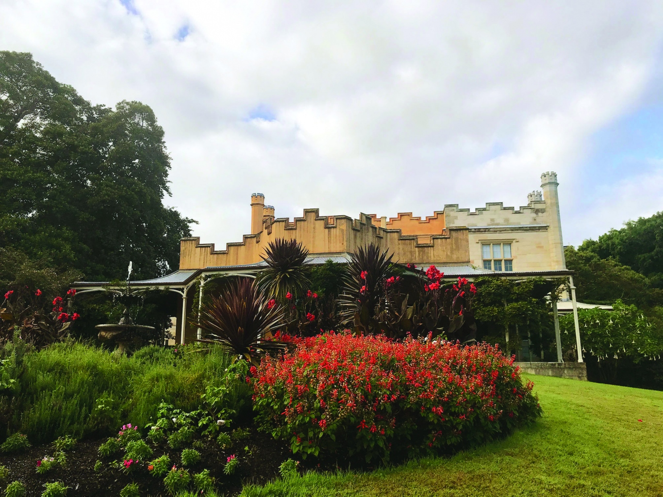 Crenellated facade of house with turrets above and colourful garden bed in foreground.
