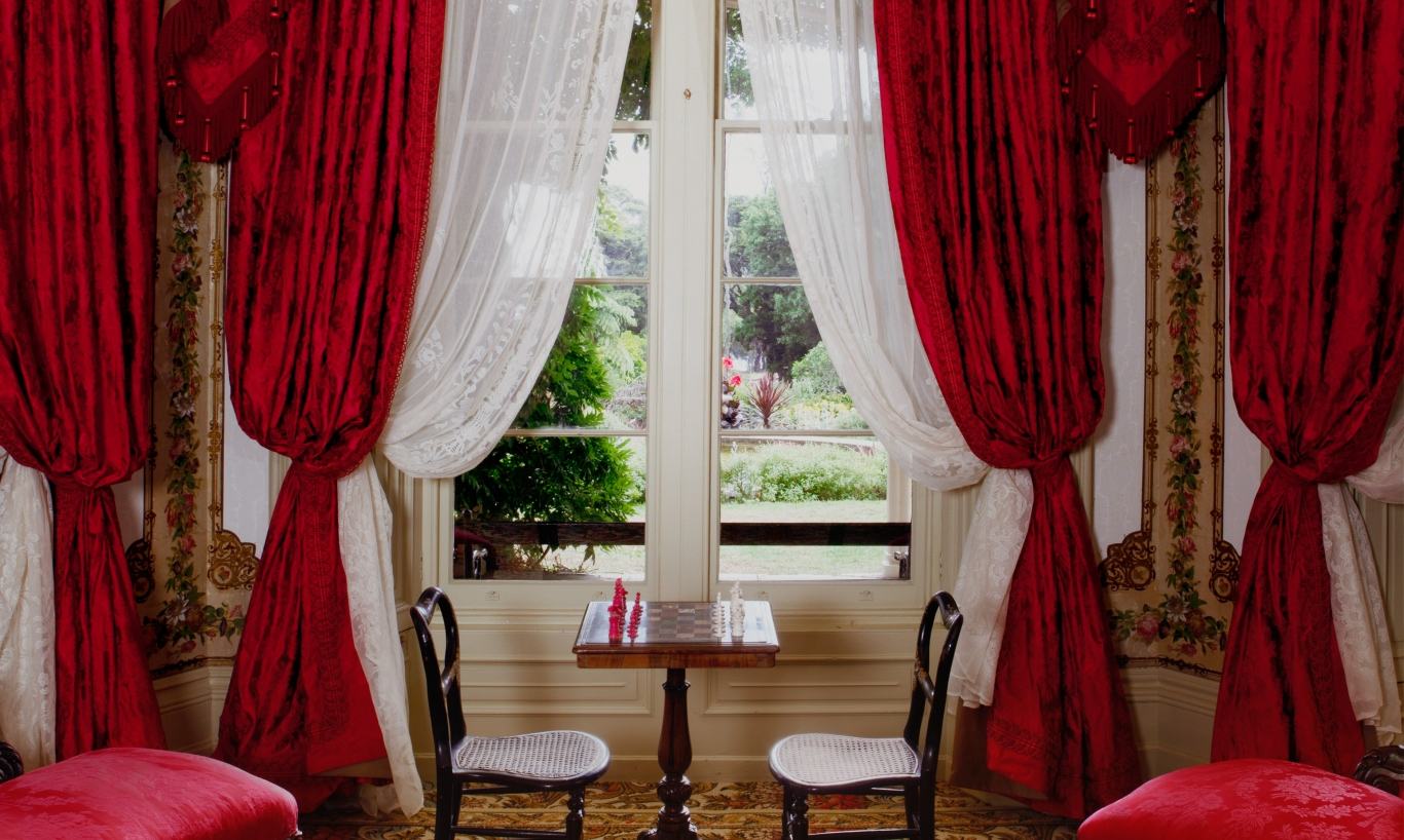 Lavishly draped windows behind drawing room furniture.