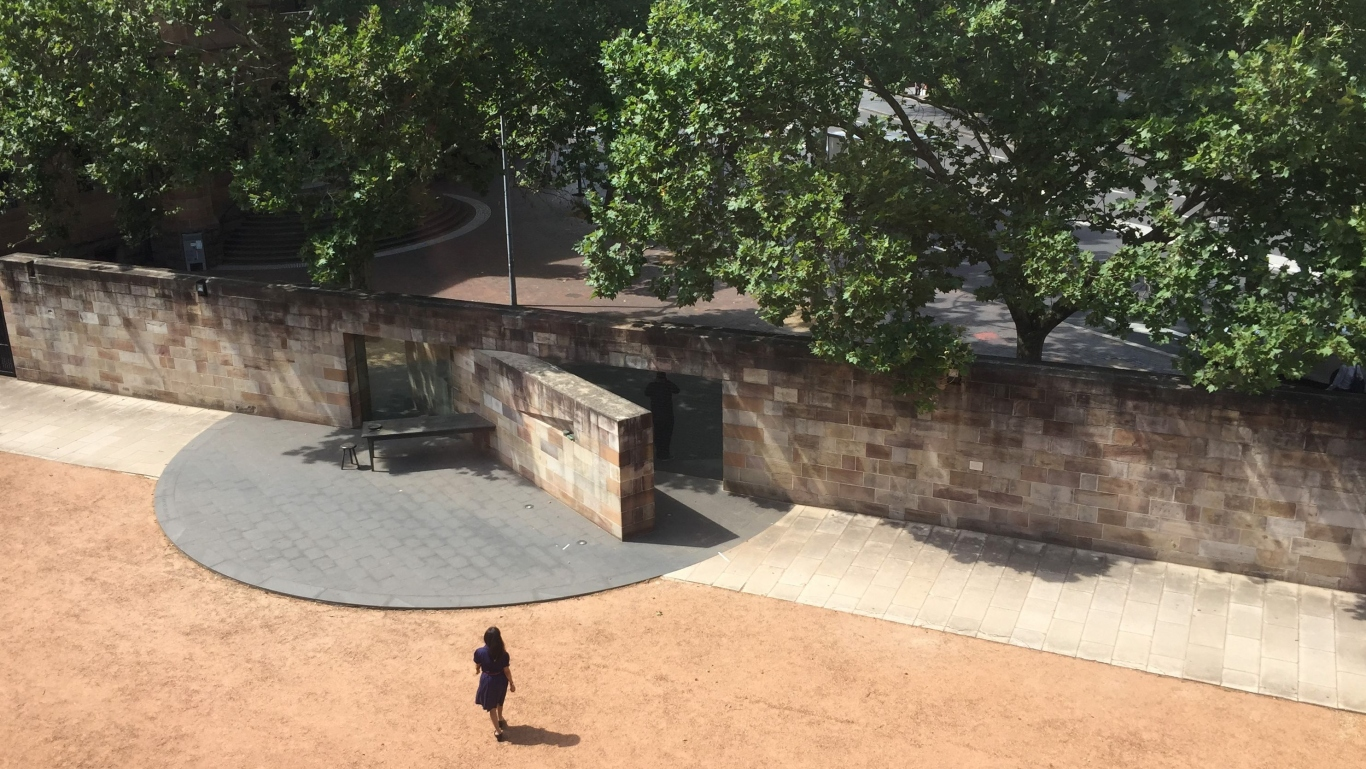 View from above of courtyard wall with monument inset and trees overhanging.