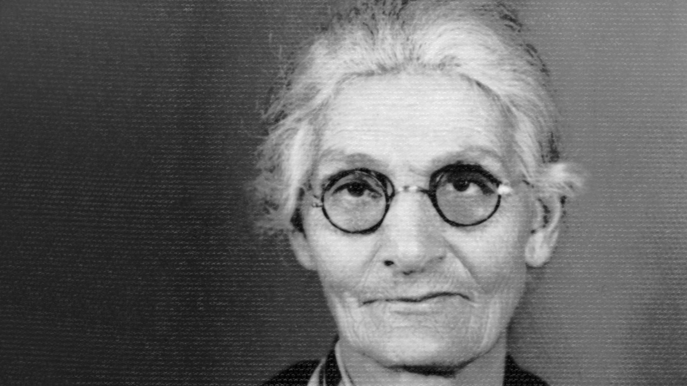 B/W identification portrait (detail) of elderly women with grey hair and small round glasses looking into camera.