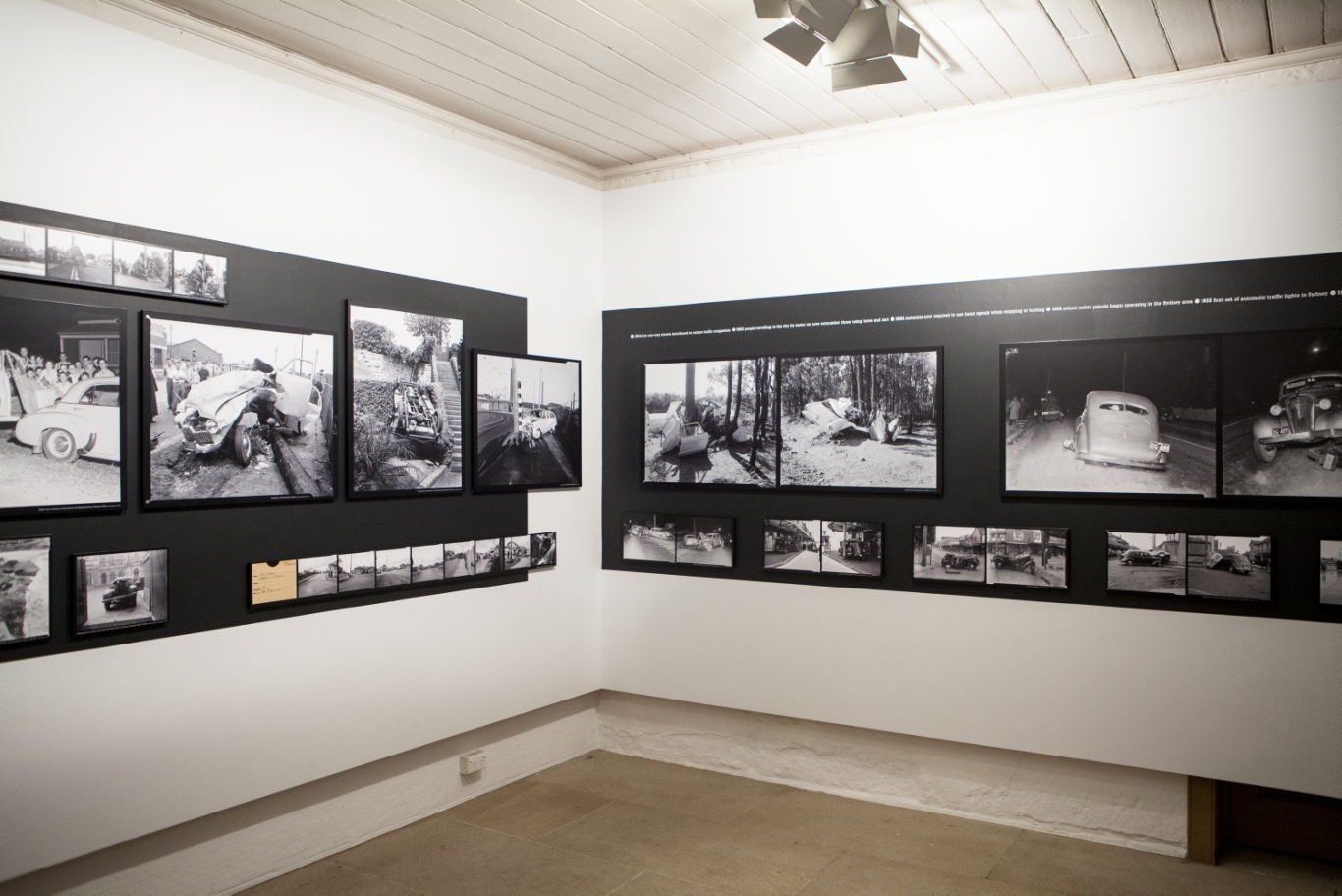 View of gallery space with black and white photographs mounted on white walls.