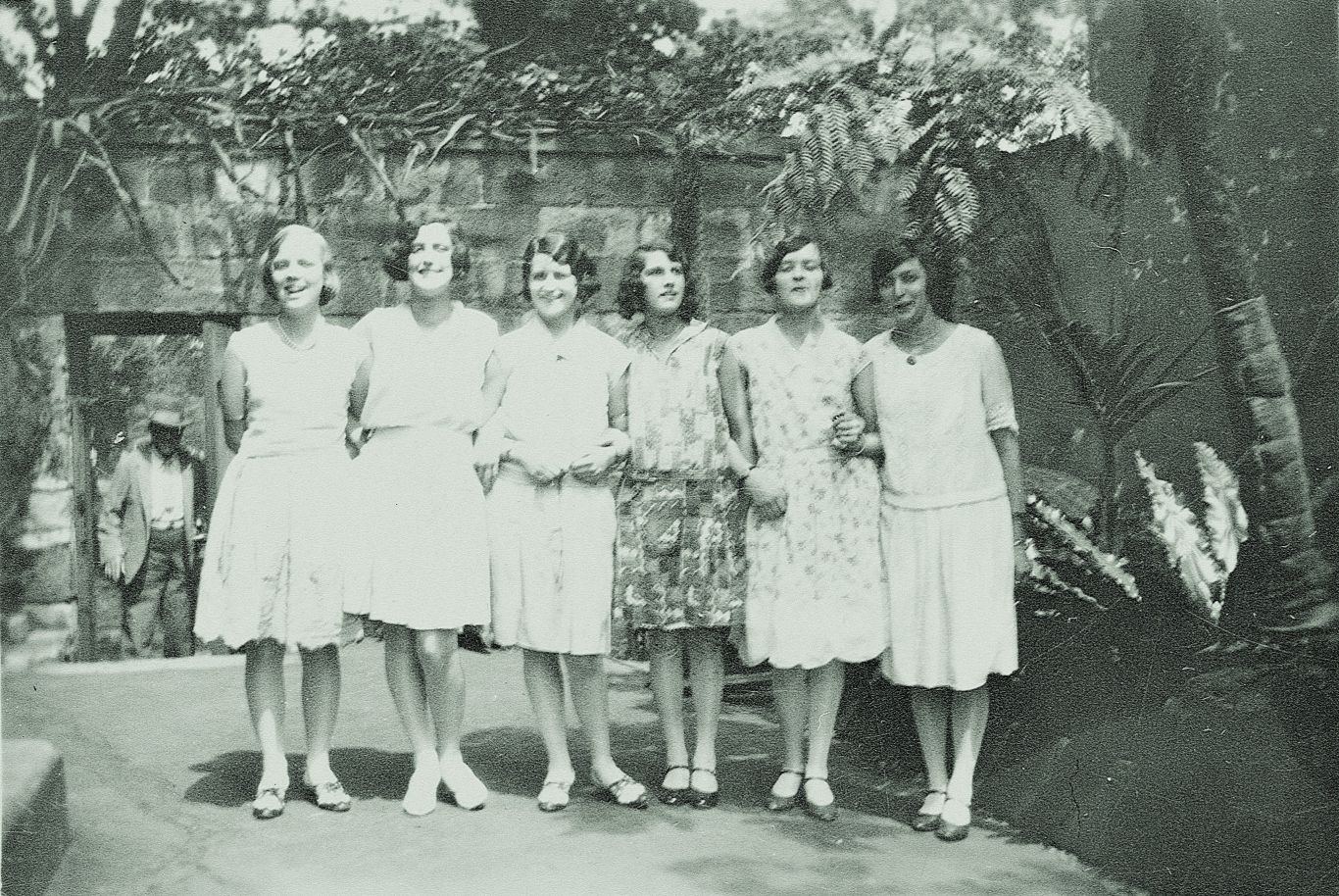 A group portrait of 6 women standing in front of a stone wall with shrubs growing over it. The women have linked arms and are all smiling at the camera.