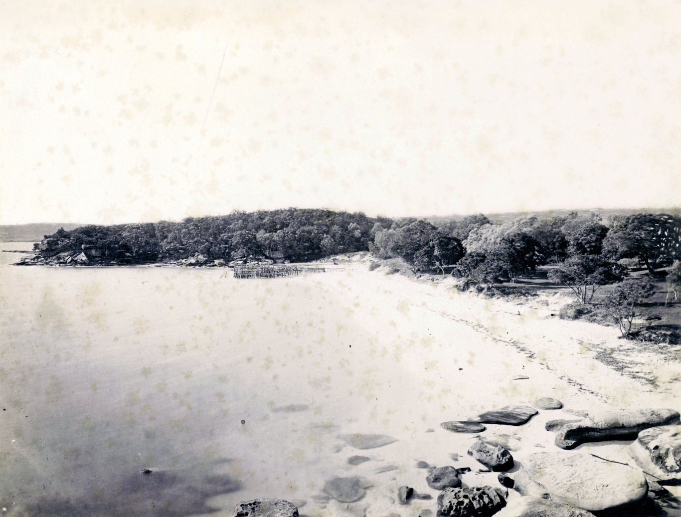 B/W photo showing a beach-lined bay with rocks and some kind of makeshift swimming enclosure at the water's edge.