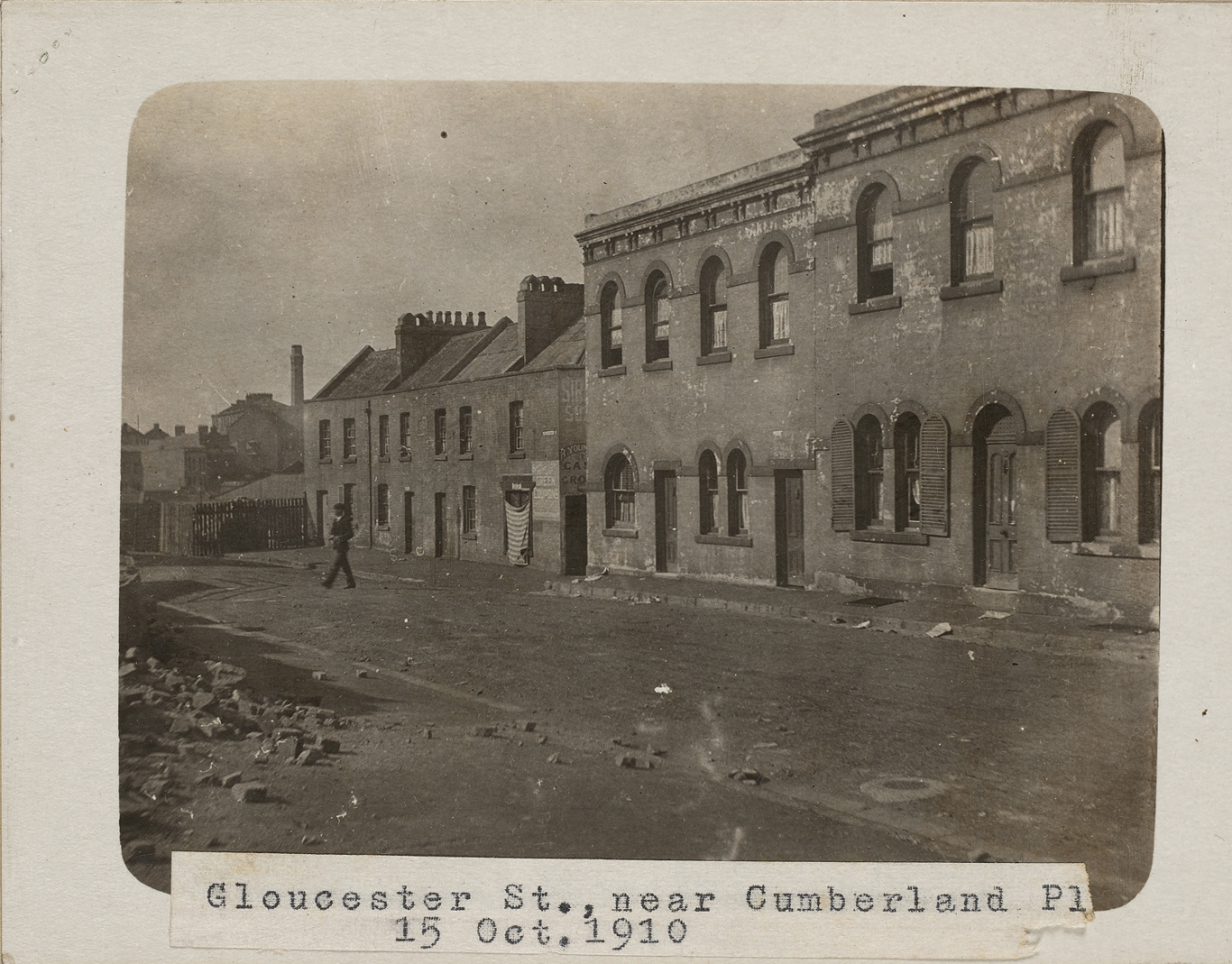 Black and white photograph of Gloucester Street showing Susannah Place terraces; The Youngein grocer shop has a stripped curtain hanging over the window.