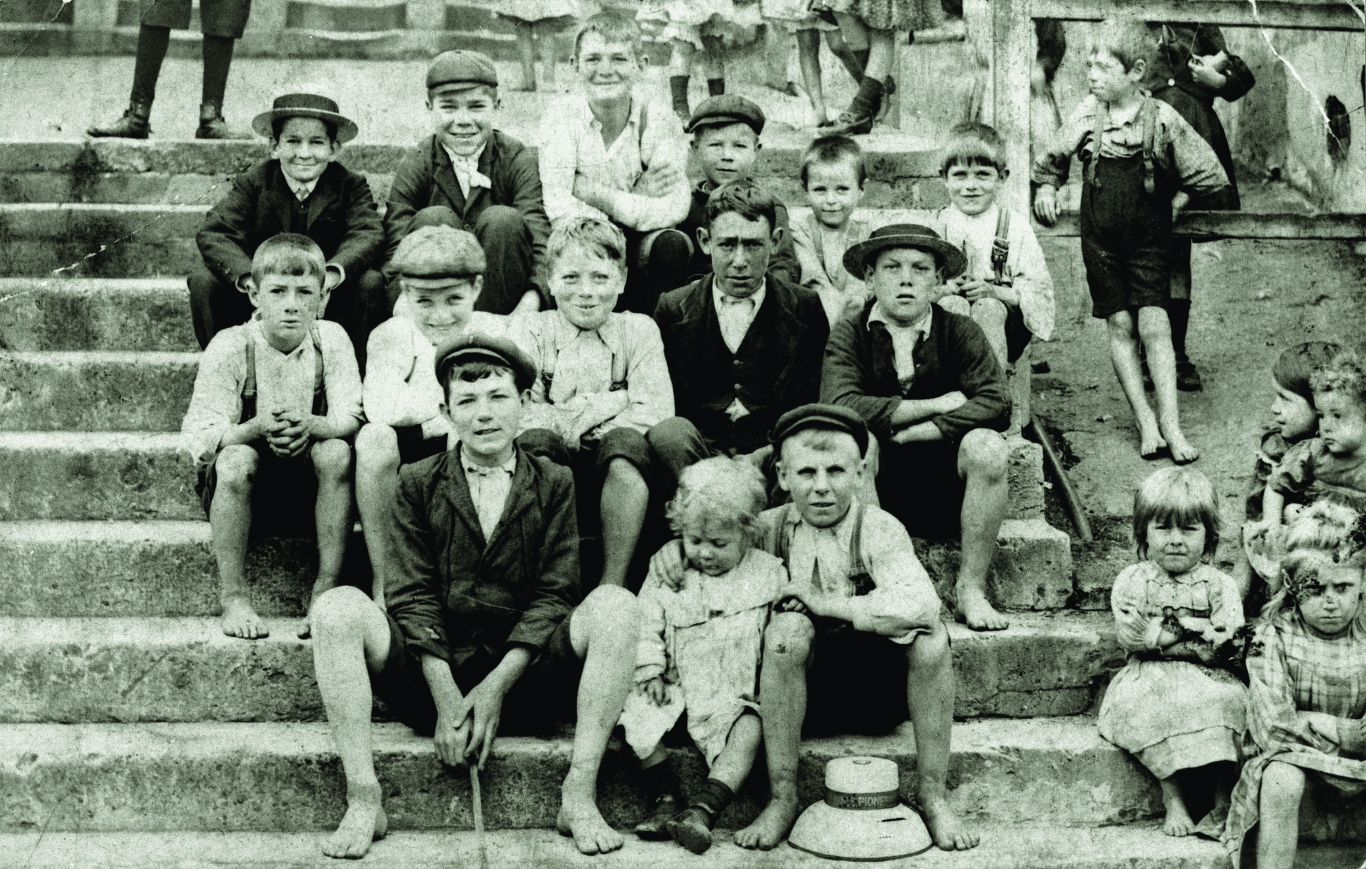 Large group of children posing for black and white photograph on the Cumberland Place steps in Sydney's Rocks area, taken around 1915