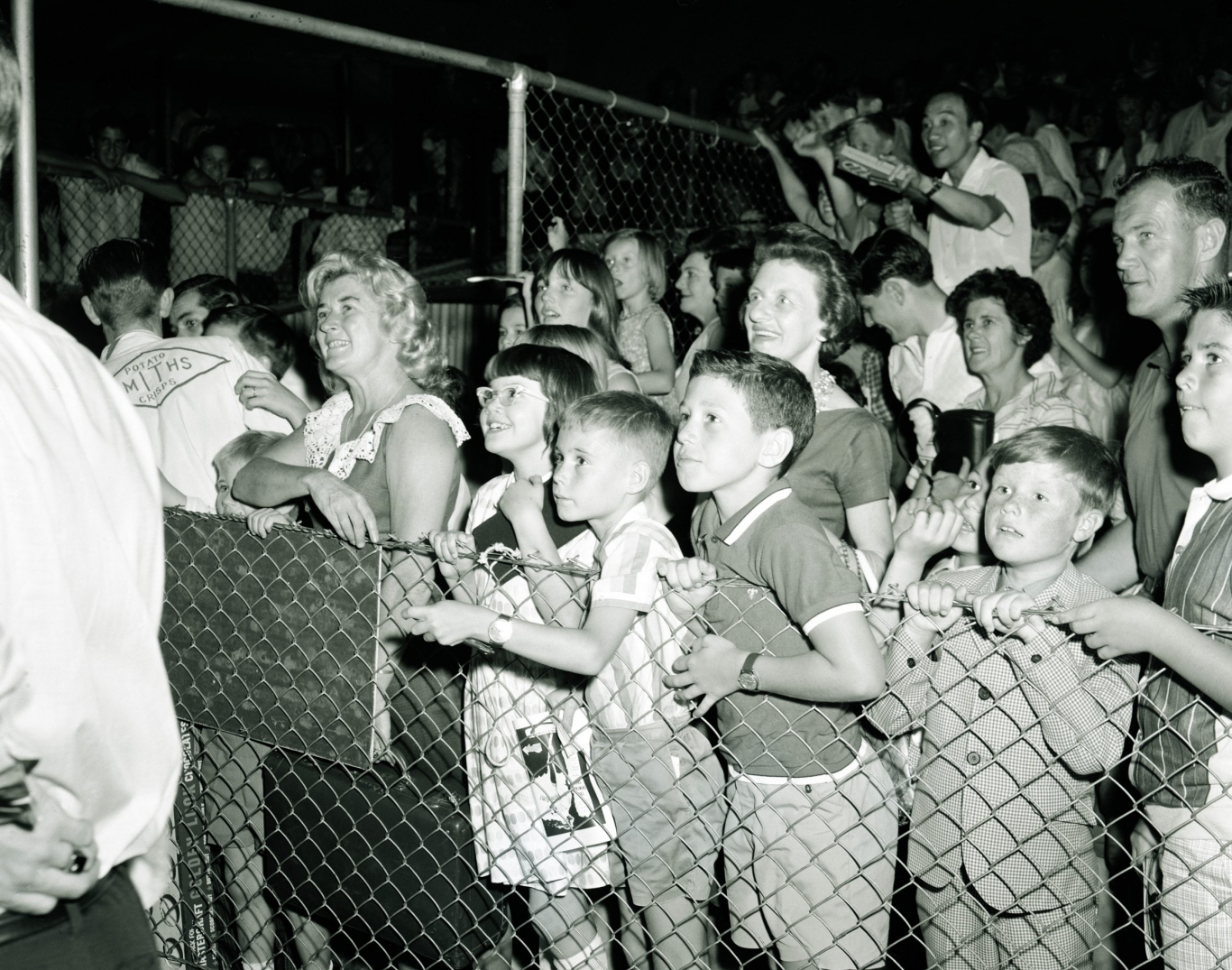 Young children and adults push at a wire fence watching a performance at the stadium.