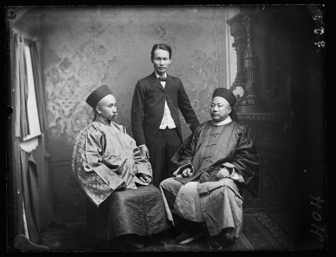 Black and white photograph of two seated men flanking a central man standing.
