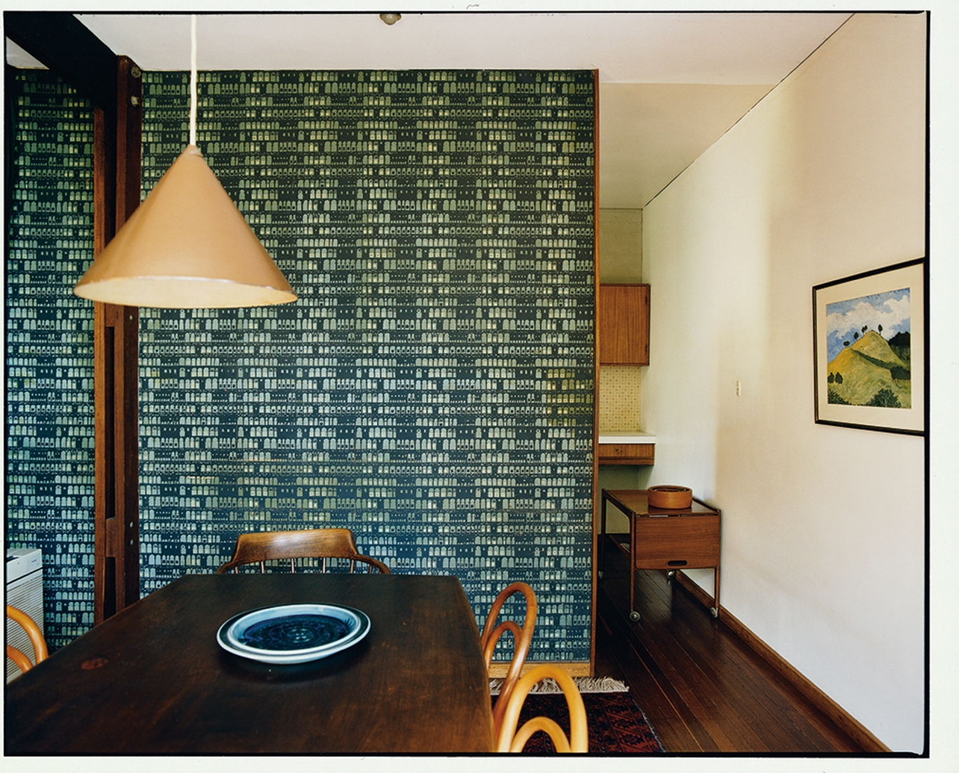 This is a photograph of a pendant light hanging over a dark timber dining table with a patterned wallpaper in the background