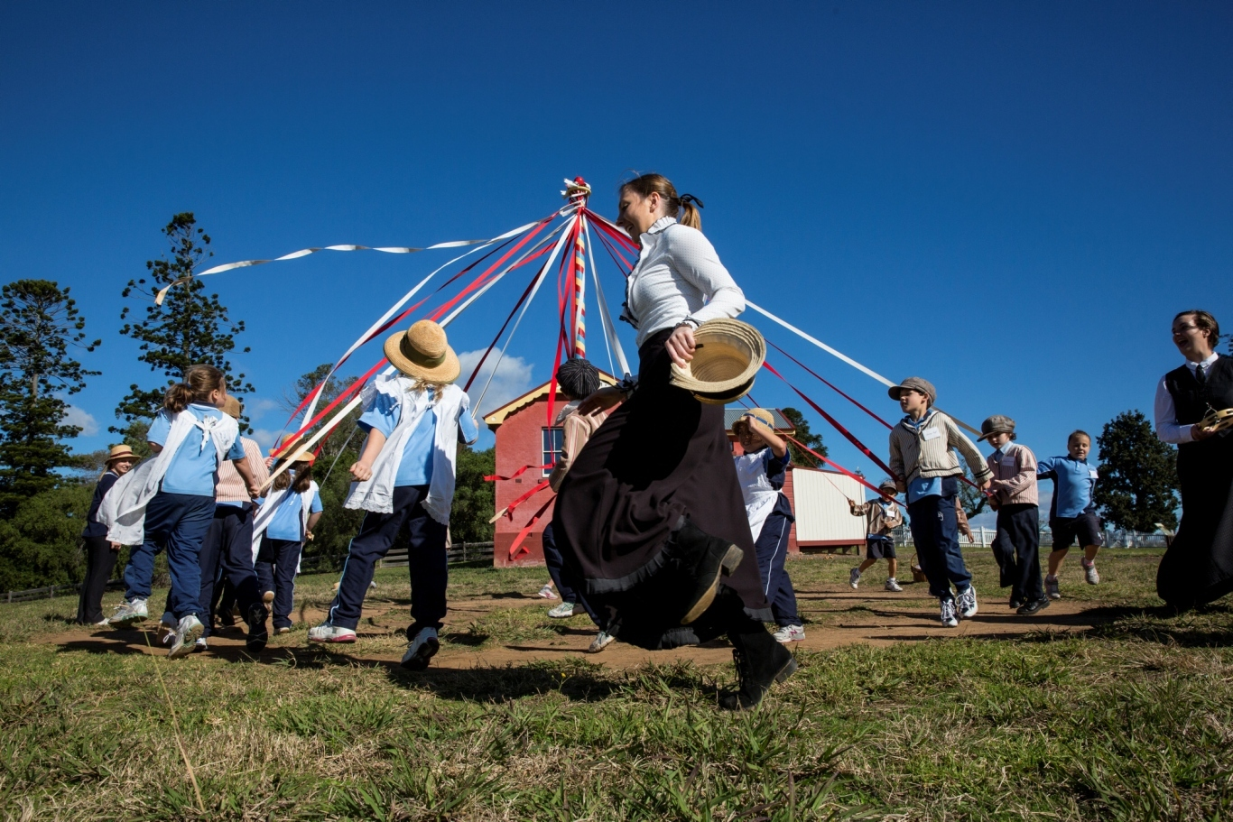 Students and adults dancing around maypole