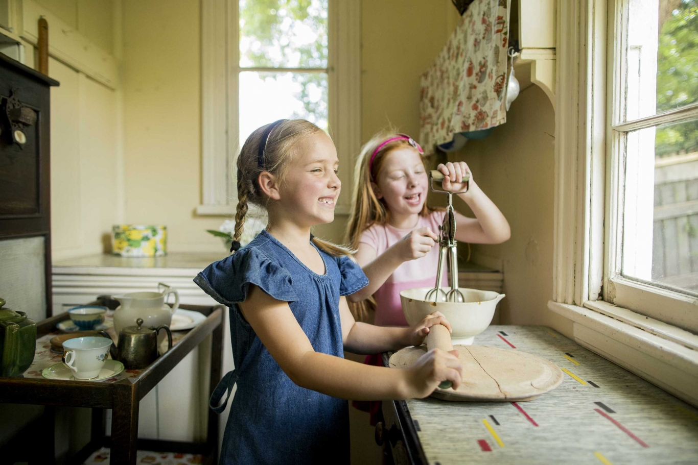 Two children in old-fashioned kitchen using implements in front of window.