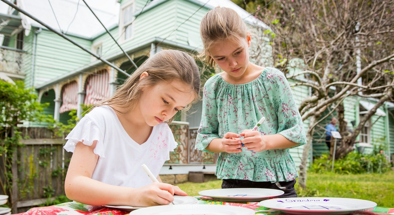 Two girls in garden setting drawing on plates.