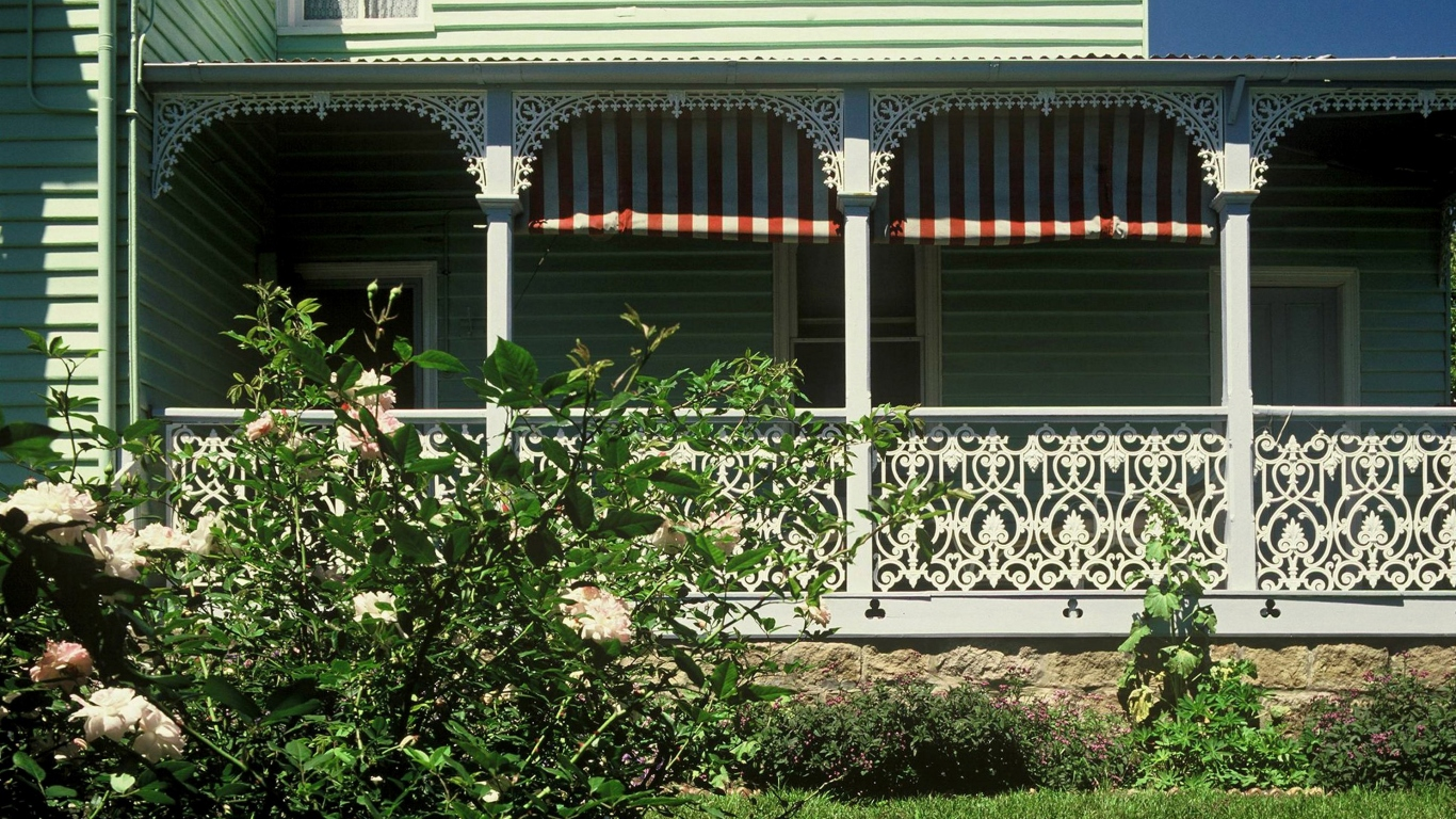 Detail of verandah at historic house Meroogal with red and white striped blinds rolled up showing green painted weatherboards and white iron work and posts.