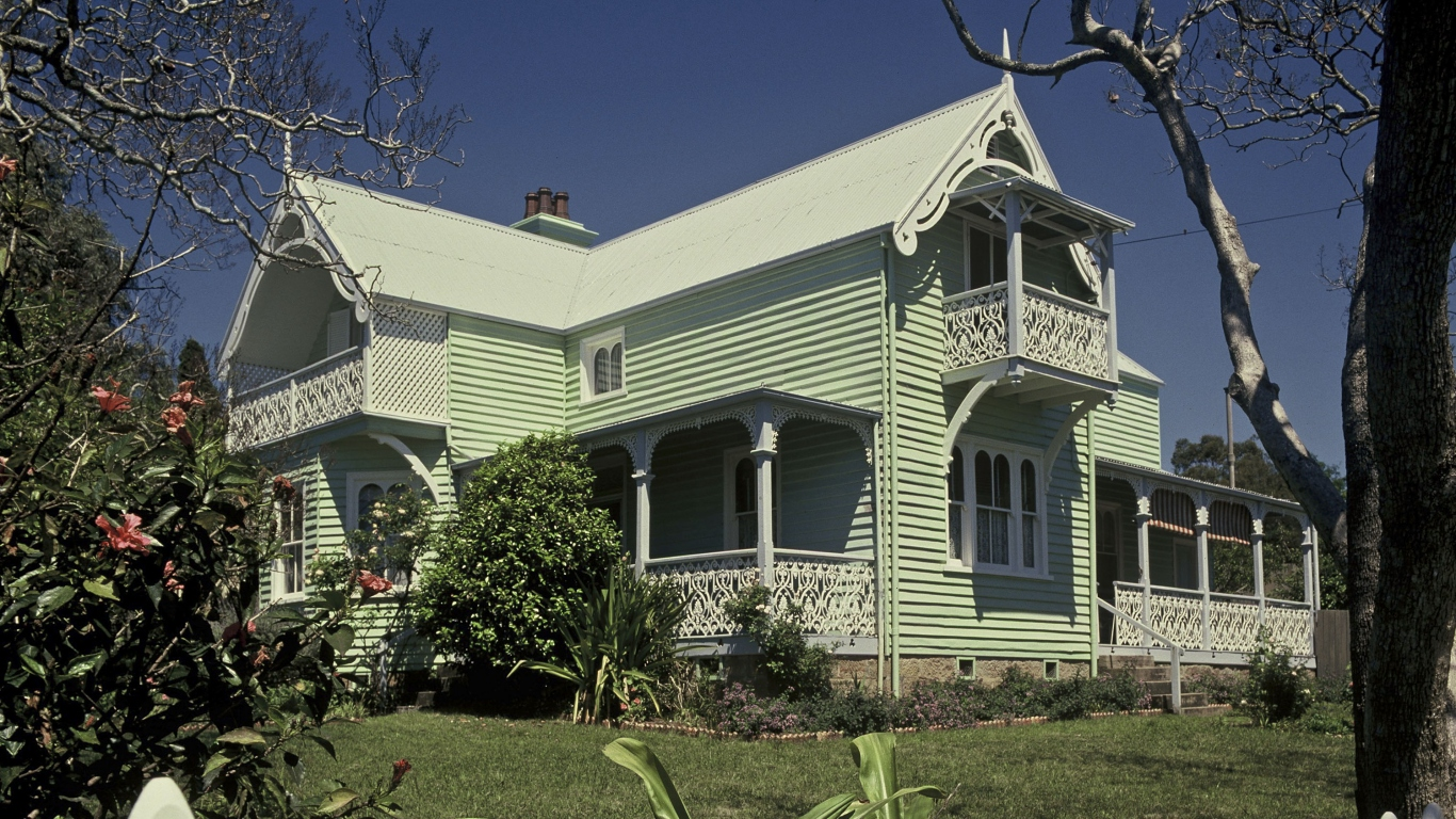 Large green weatherboarded house, two storeys, surrounded by lush gardens and trees. The house has high pitched gables and verandahs.