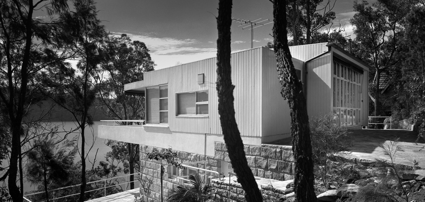 Black and white photo of modern house in bush setting.