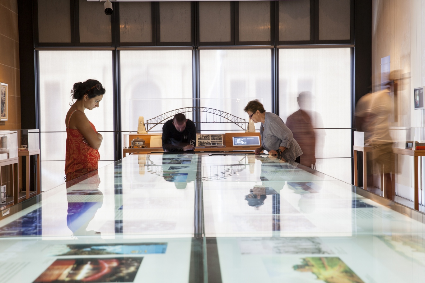 Image of visionaries exhibition. A long display case stretches out in front of the camera and people are leaning over and reading.