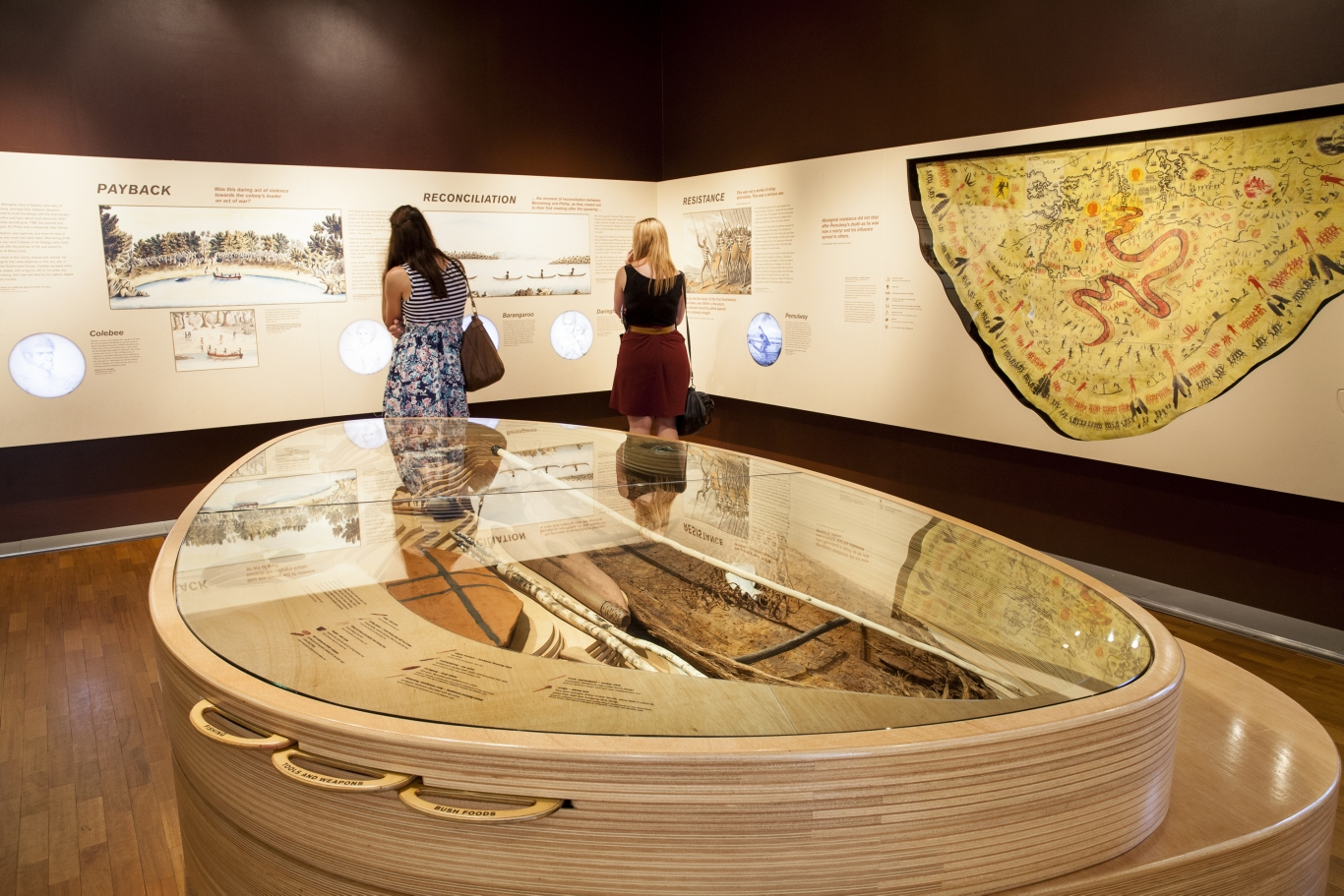 Visitors look at the Gadigal place display. Image shows a large showcase in the middle of the room with people reading text and looking at objects on the wall around the room.