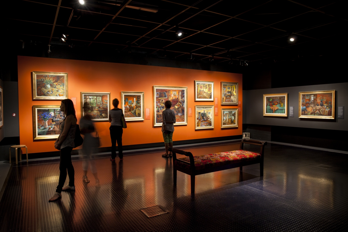 Photo of a darkened gallery with Margaret Olley paintings on the walls. Visitors are standing in the space.