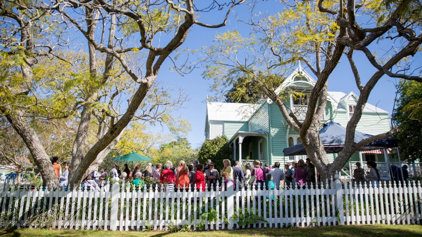 Large gathering in garden around wooden house, surrounded by white picket fence.