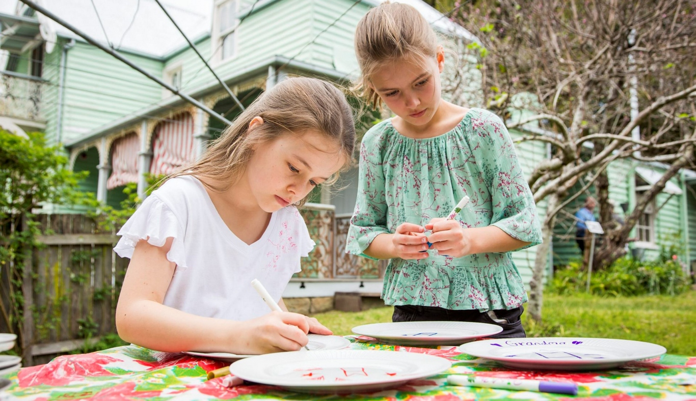 Two little girls decorating plates at Meroogal  house