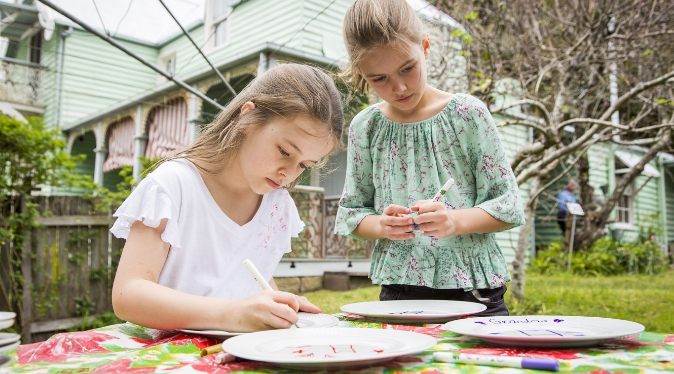 Two girls decorate ceramic plates at Meroogal