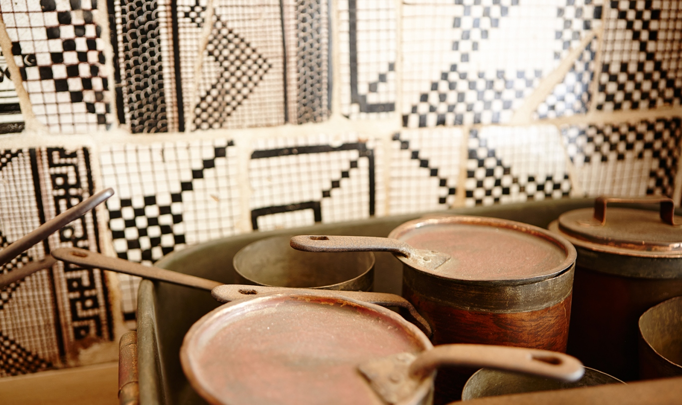 Pots and pans in the foreground and mosaic tiles on the wall