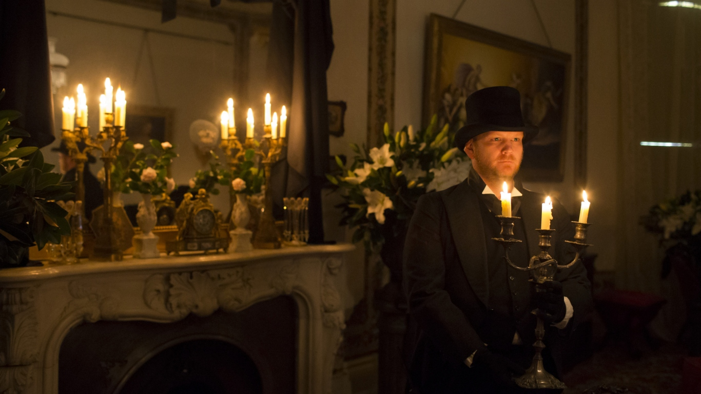 Man holding lit candelabra in candlelit room draped in black.