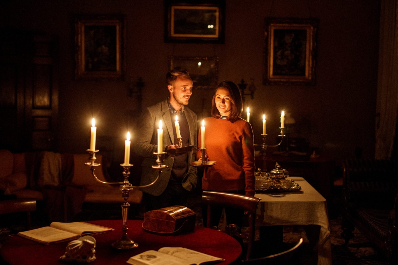 Two people in ornately furnished room, lit by candle light.