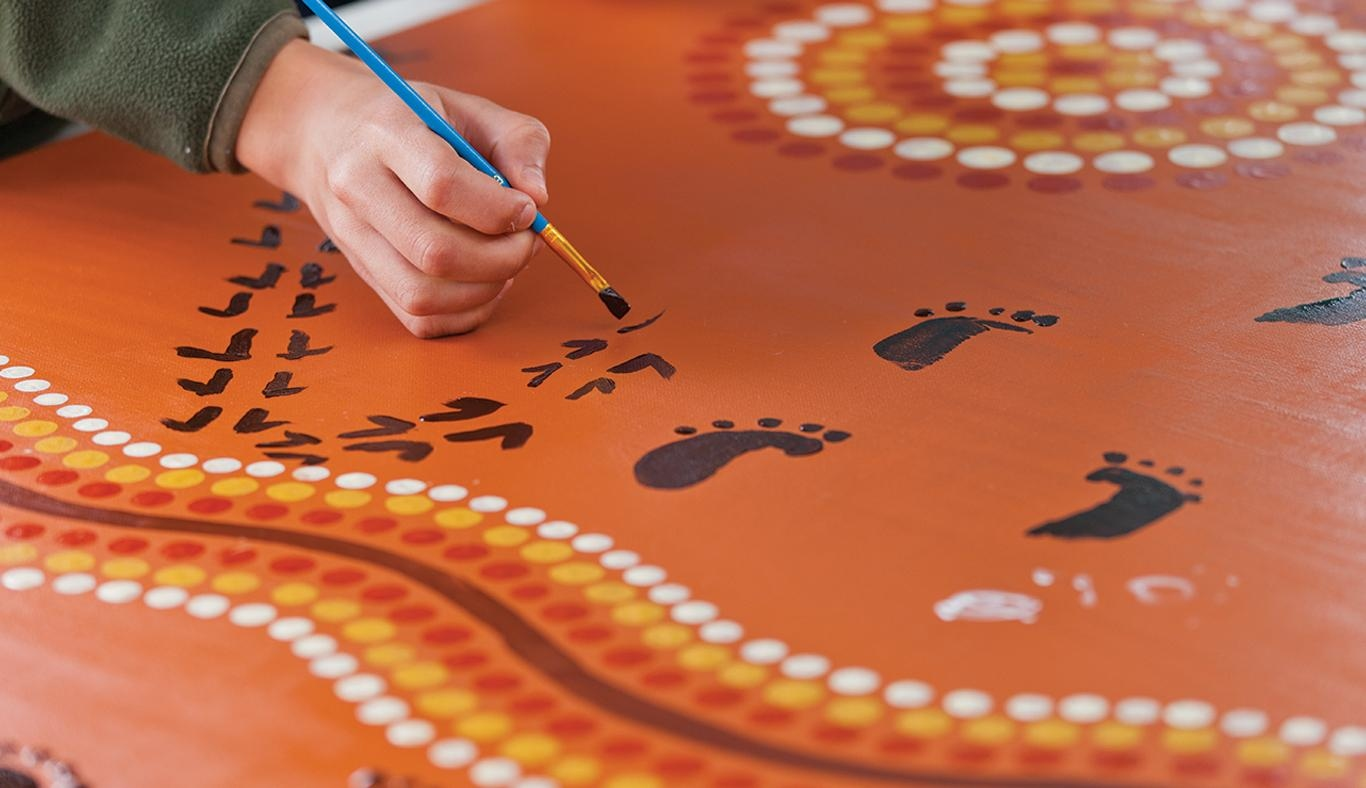 Indigenous painting with hand and paintbrush in foreground