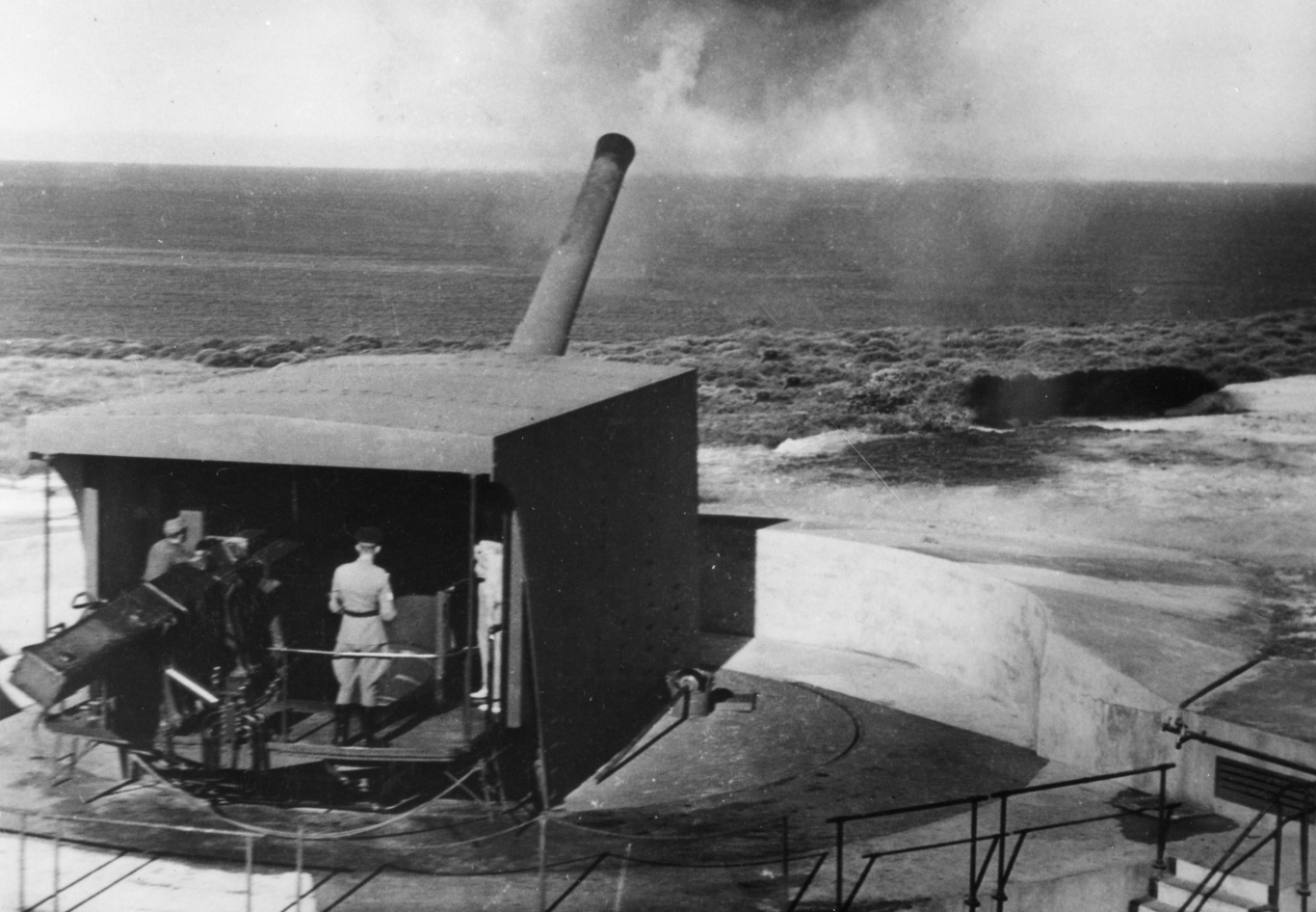 Black and white image showing a large gun emplacement with a gun firing.