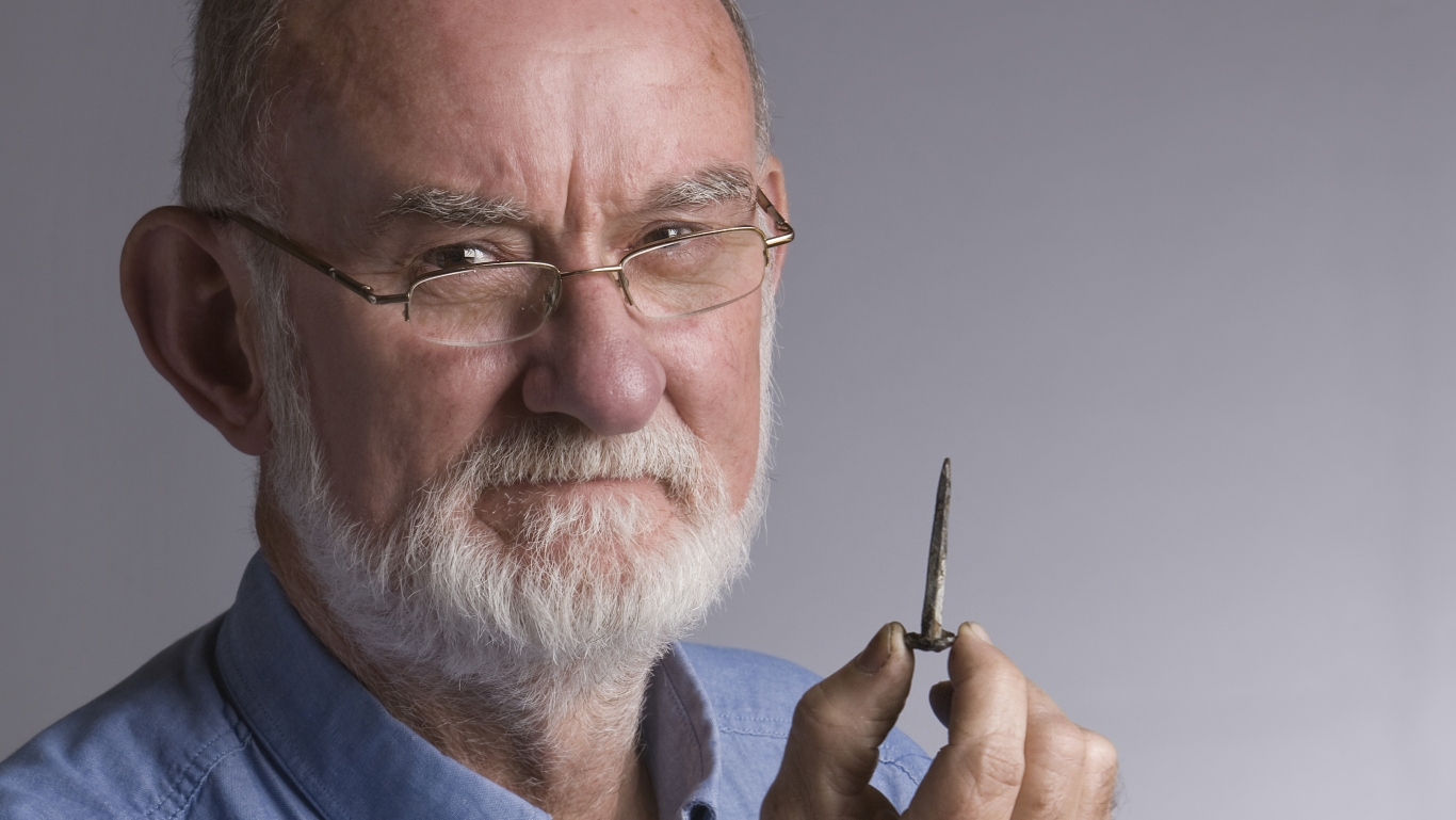 Man with glasses and grey beard, with intense look, holding a nail between his fingers
