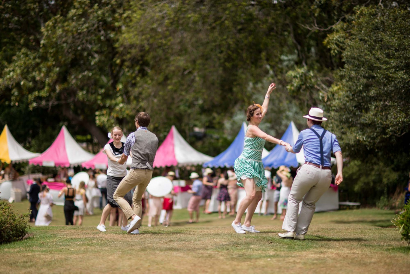 Couples wearing vintage clothing dancing on the lawn with colourful marquee and crowd in background.