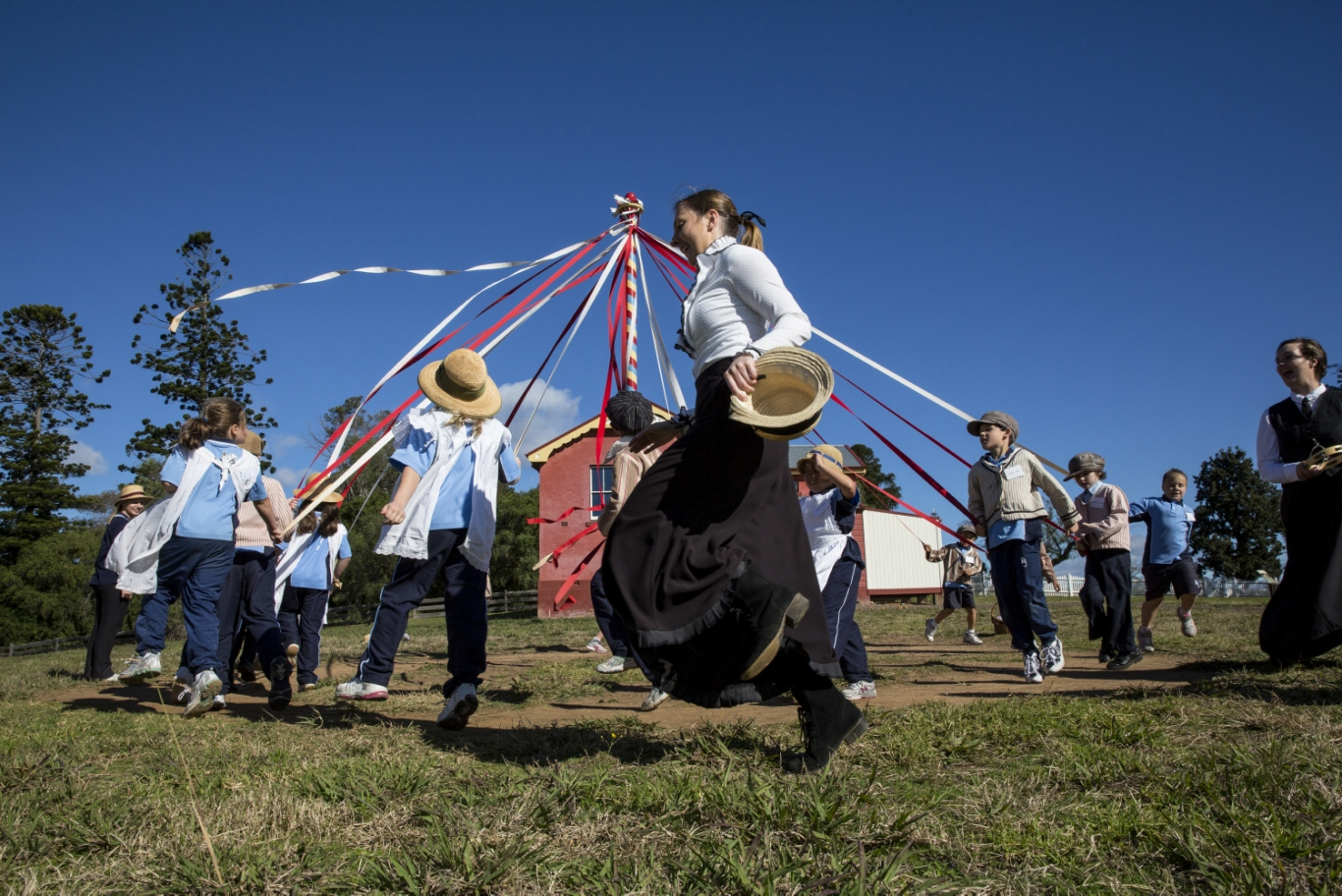 Adults and children dressed in period costume dancing around maypole holding onto ribbons in outdoor setting with schoolhouse in background.