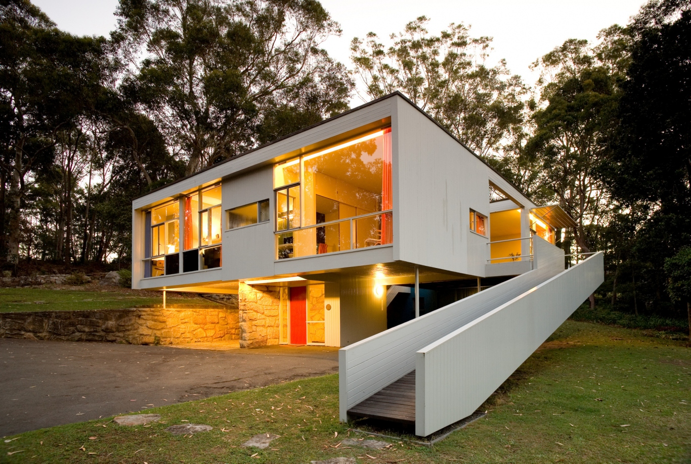 Modernist house with lights on against bush backdrop.