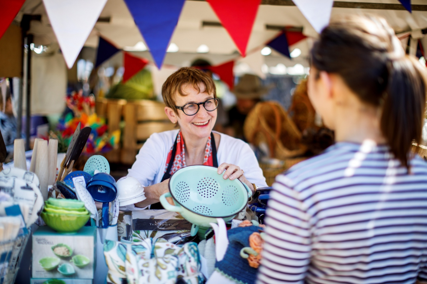 Woman in market stall holding up colander to show customer.