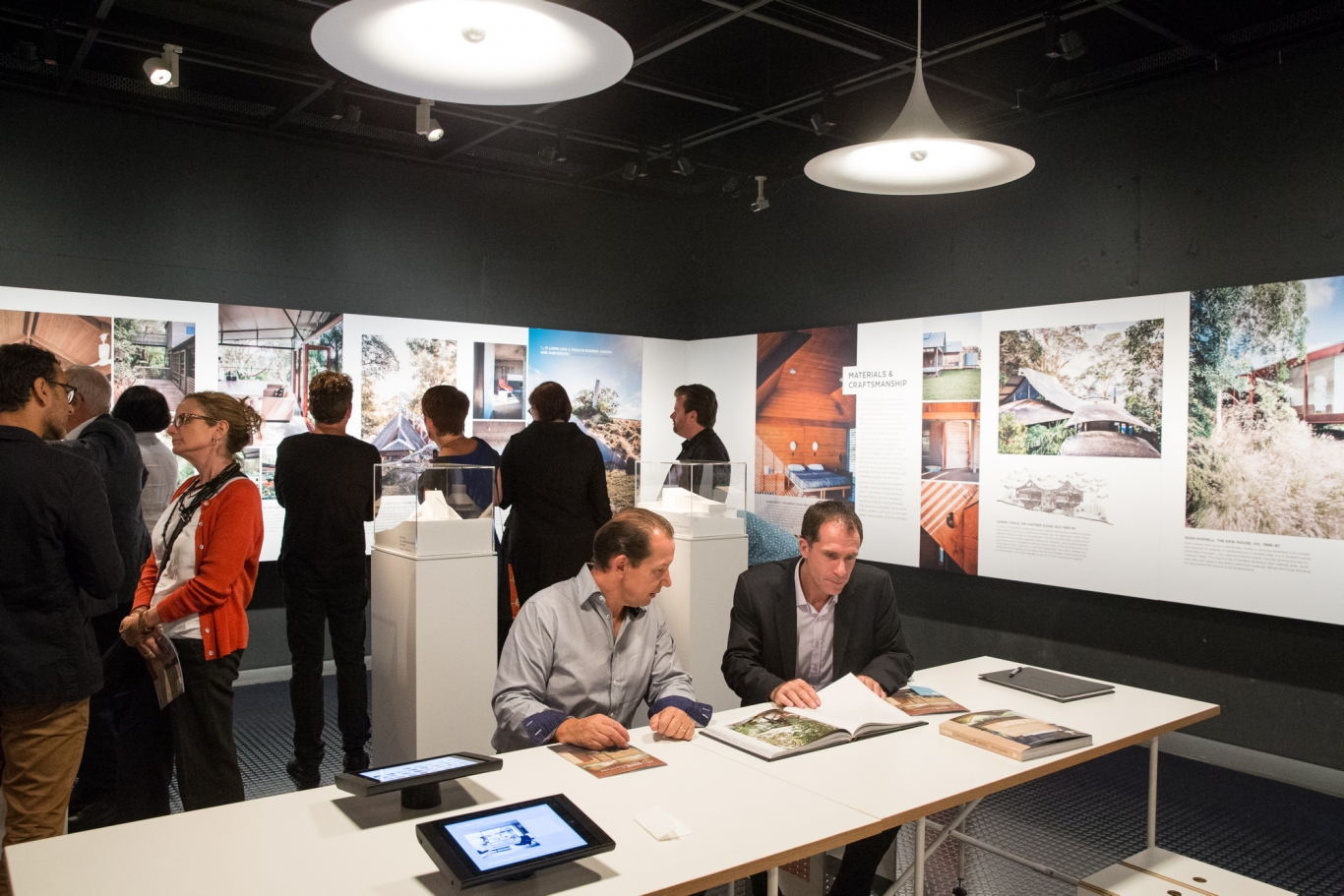 This is a photograph of a colleciton of people inside the exhibition looking at panels, sitting at tables and reading books or looking at iPads