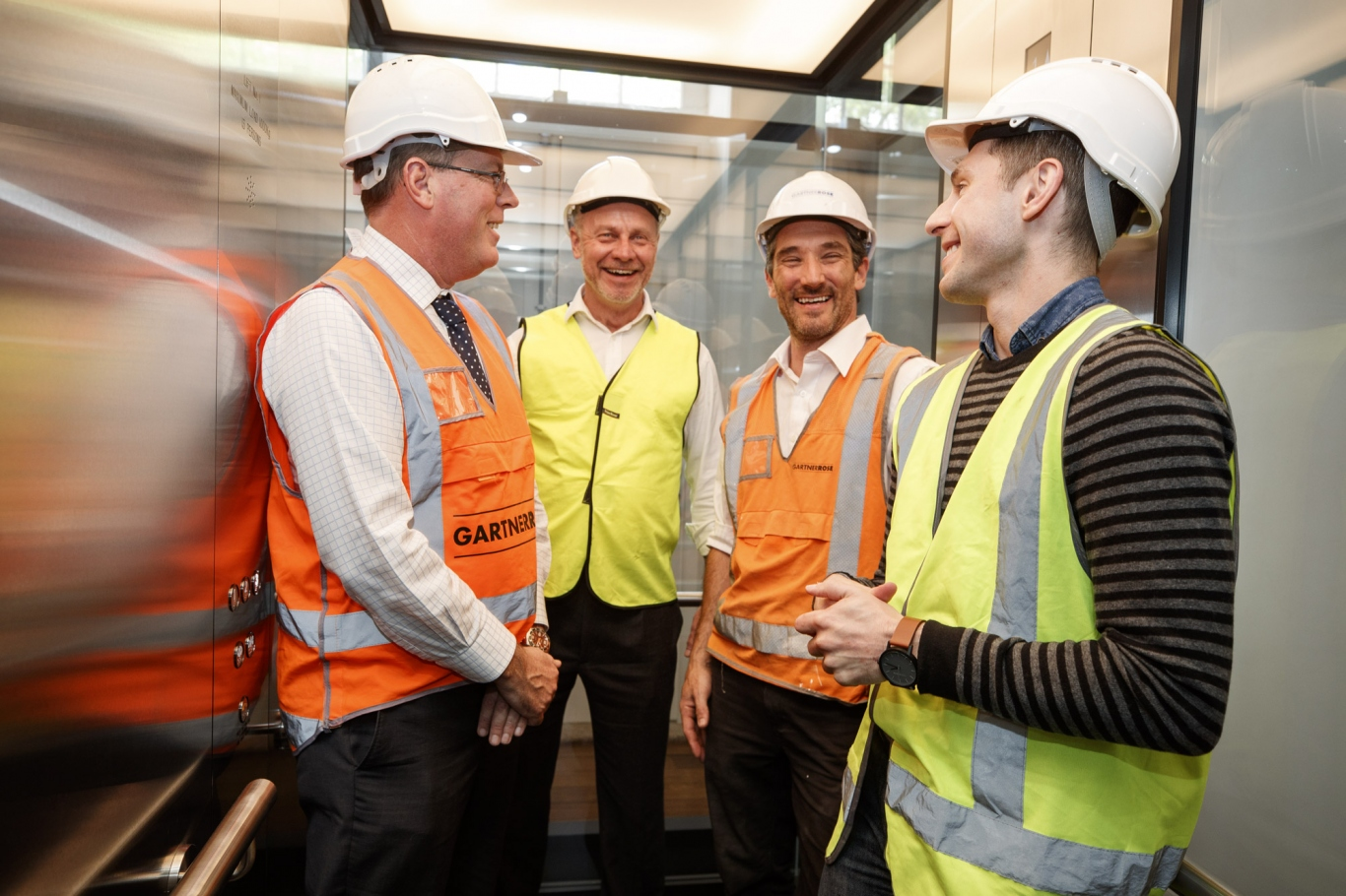 Group of four men in white hard hats and high vis vests in glass lift.