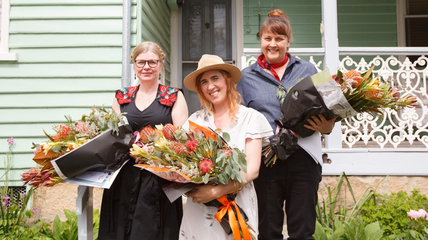 Three women holding bouquets outside house.