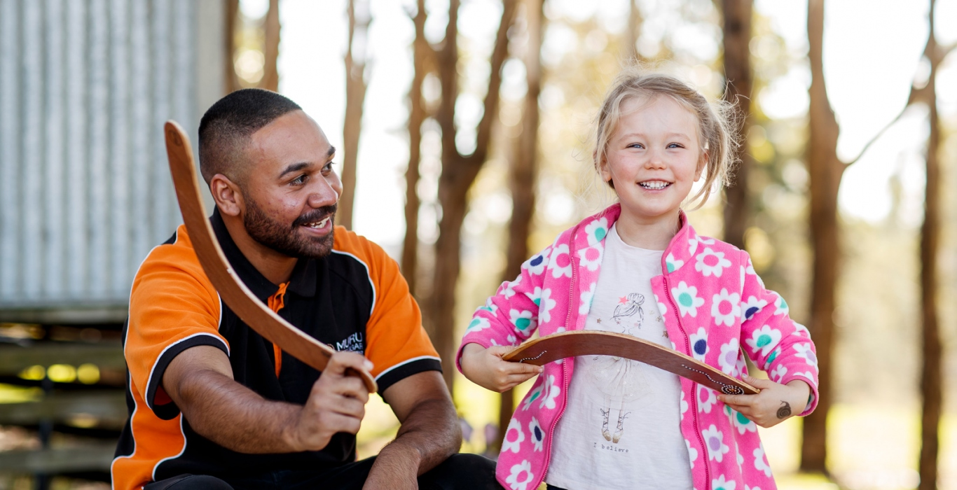 Man showing girl how to use a boomerang.