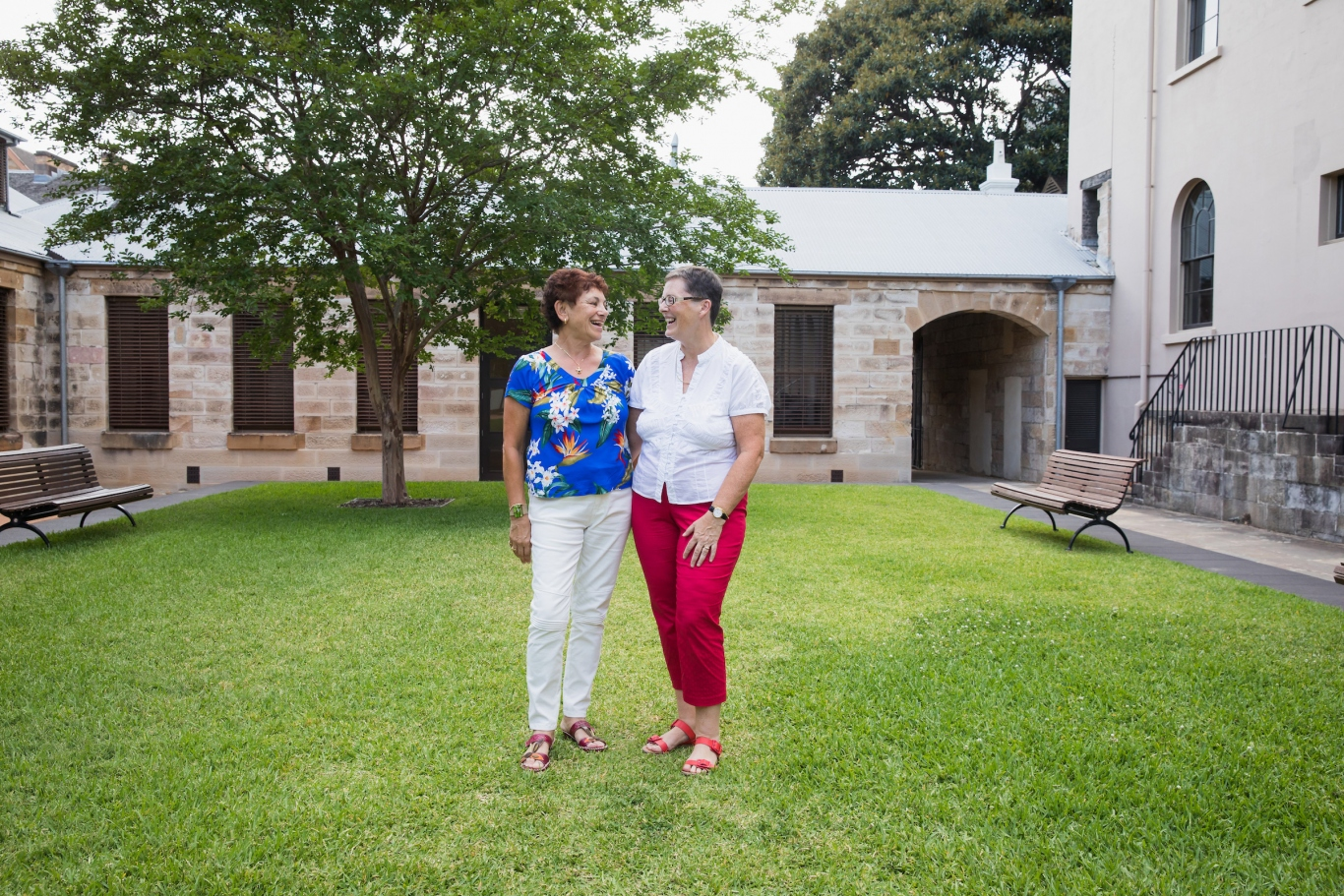 Two women standing on lawn within sandstone courtyard.