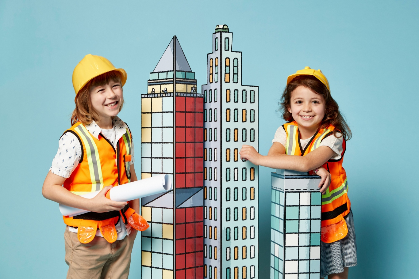 Two kids dressed in hard hats and hi-vis vests with model of cityscape.
