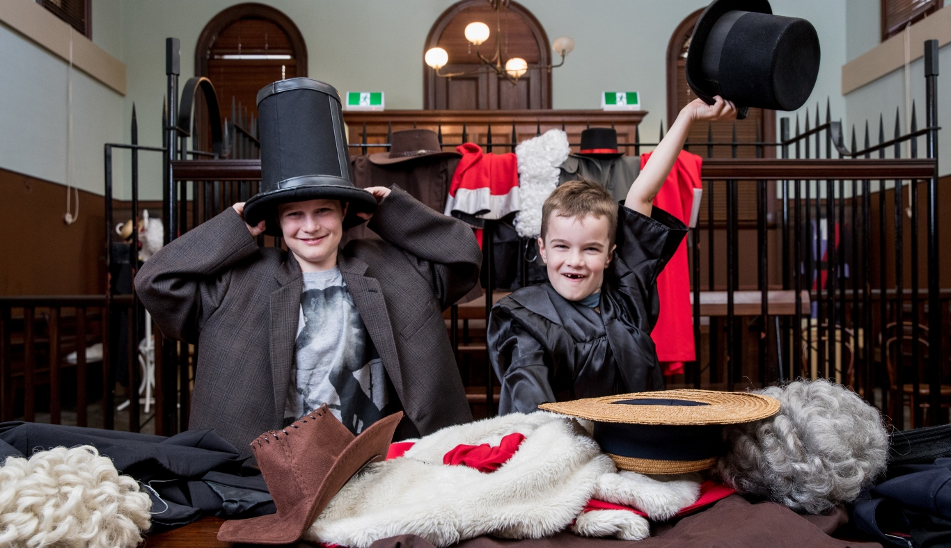 Two little boys dressing up in an old court room