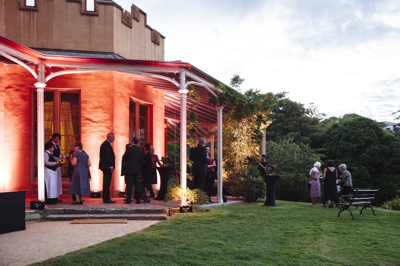 Exterior of house in early evening with lighting on verandah with gathering of people.