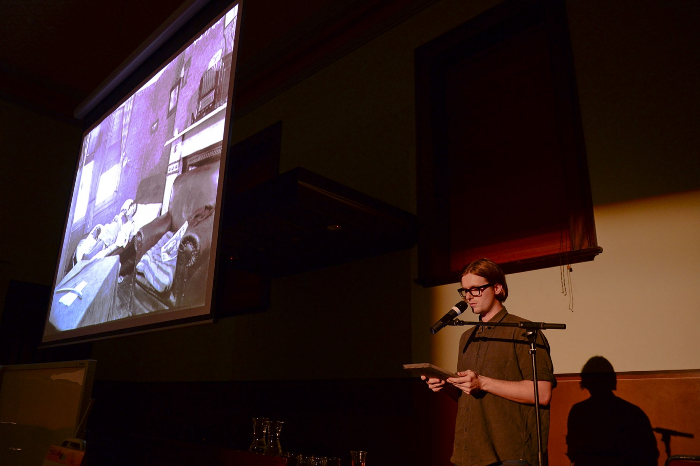 Image of a man at a microphone with a screen projecting an image of a deceased woman lying on a bed