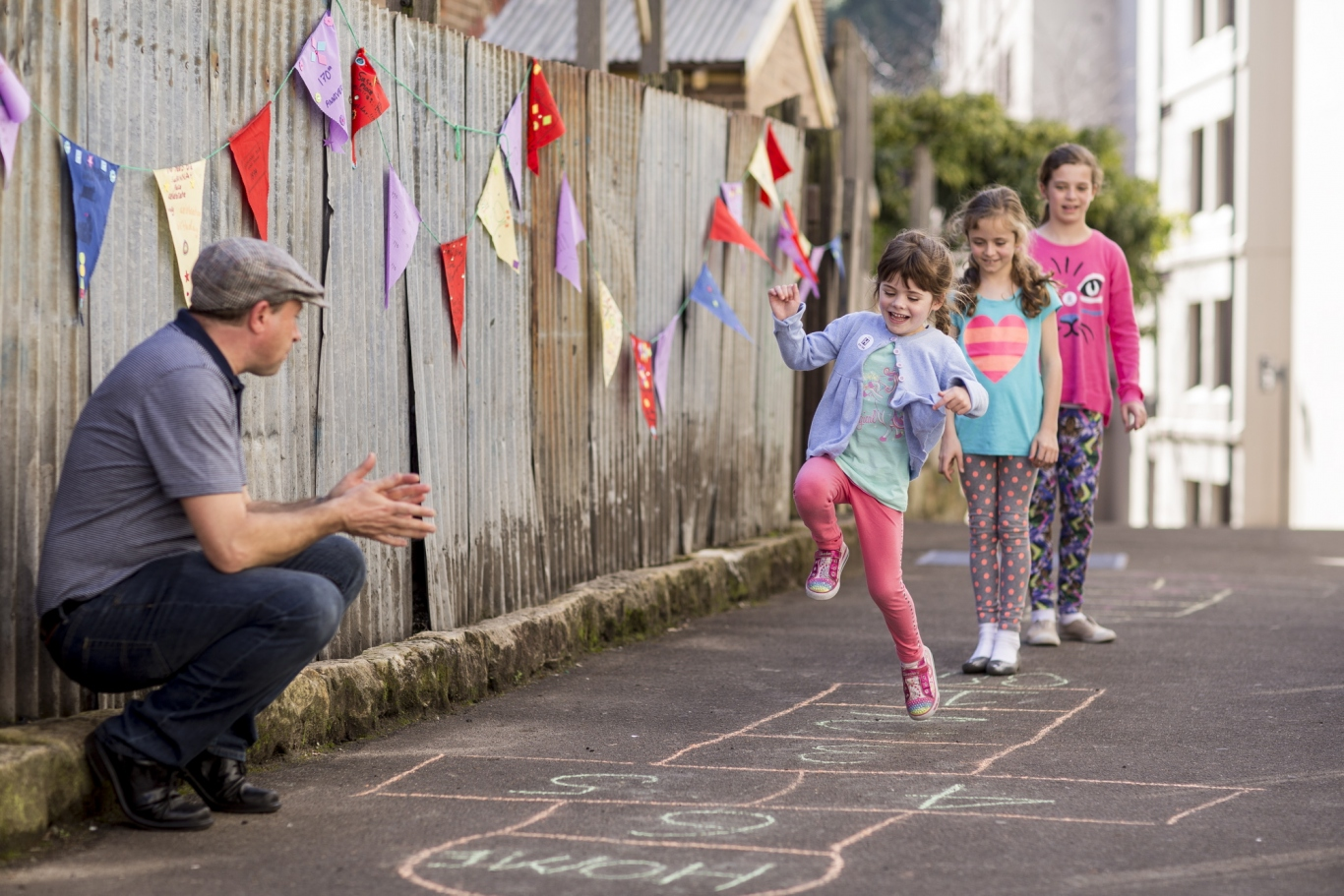 Charlotte, Coco, Chloe, Shelbi and Lani Rae playing hopscotch in Cambridge Street with volunteer Dominic Dwyer looking on